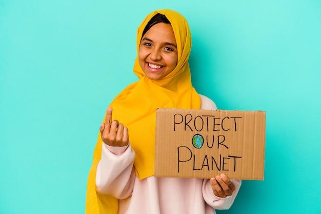 Jonge moslimvrouw met een bescherm onze planeet geïsoleerd op een blauwe achtergrond, wijzend met de vinger naar je alsof uitnodigend dichterbij komt.