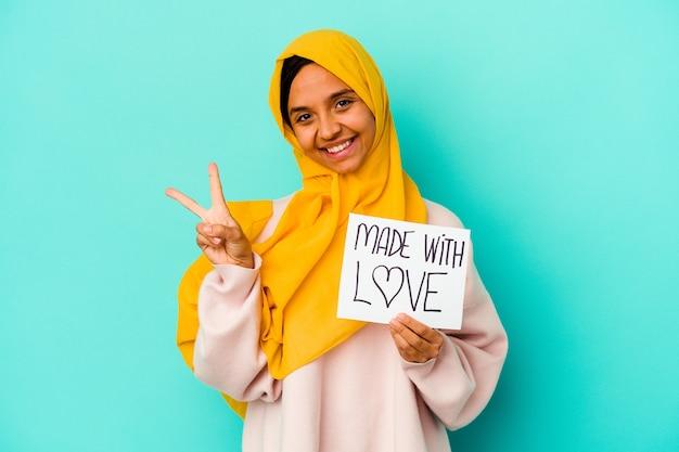 Jonge moslimvrouw met een bordje gemaakt met liefde geïsoleerd op blauwe achtergrond vrolijk en zorgeloos met een vredessymbool met vingers.