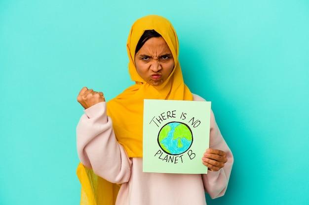 Jonge moslimvrouw met een er is geen bordje met planeet b op blauw met vuist, agressieve gezichtsuitdrukking.