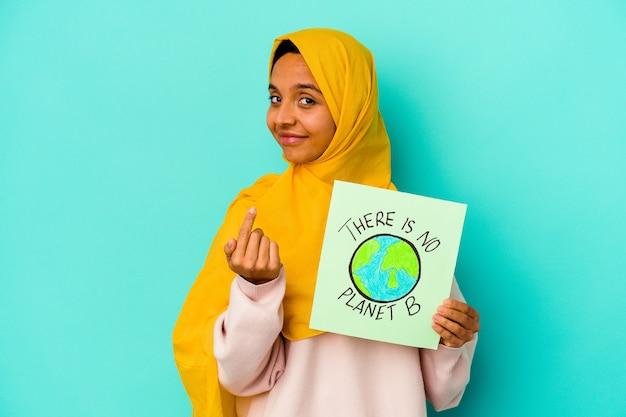 Jonge moslimvrouw met een er is geen plakkaat met planeet b geïsoleerd op een blauwe muur wijzend met de vinger naar je alsof uitnodigend dichterbij komen
