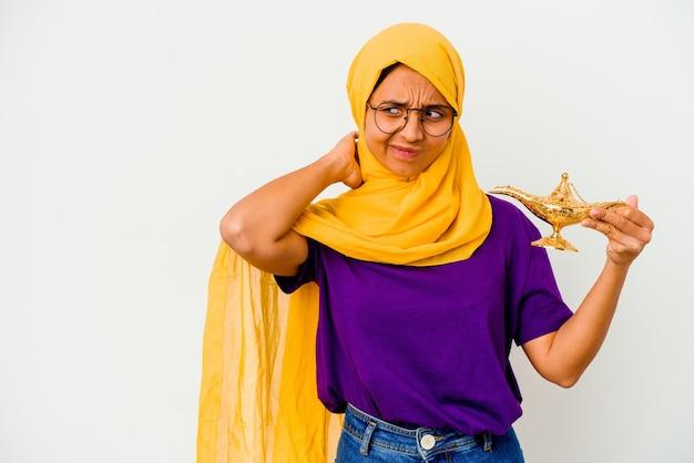Jonge moslimvrouw met een lamp geïsoleerd op een witte achtergrond die de achterkant van het hoofd aanraakt, denkt en een keuze maakt.