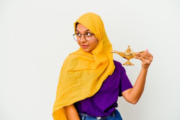 Jonge moslimvrouw met een lamp geïsoleerd op een witte achtergrond kijkt opzij glimlachend, vrolijk en aangenaam.