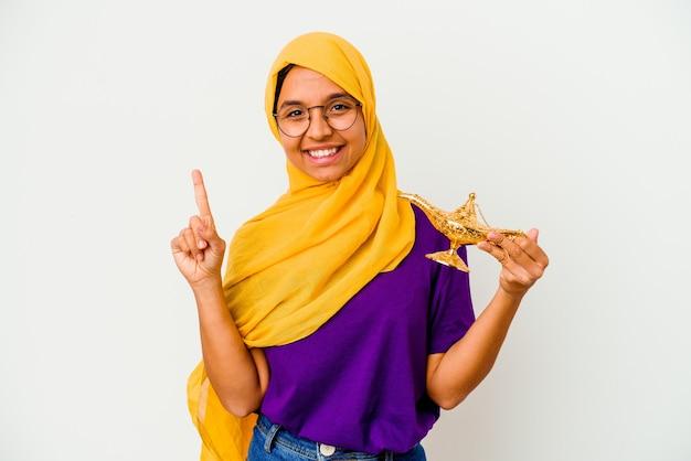 Jonge moslimvrouw met een lamp geïsoleerd op een witte achtergrond met een geweldig idee, concept van creativiteit.