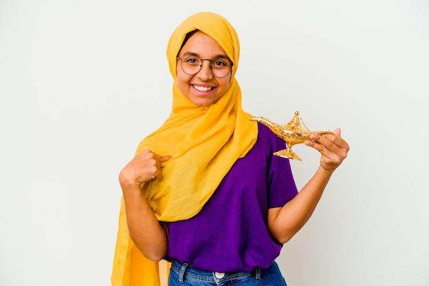 Jonge moslimvrouw met een lamp geïsoleerd op een witte achtergrond persoon die met de hand wijst naar een shirt kopieerruimte, trots en zelfverzekerd?