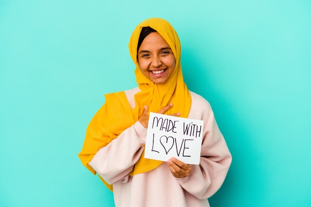 Jonge moslimvrouw met een plakkaat gemaakt met liefde geïsoleerd op blauwe muur lacht hardop hand op de borst te houden