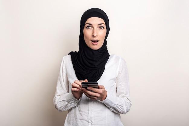 Jonge moslimvrouw met een verbaasd gezicht in een hijab houdt een telefoon in haar handen