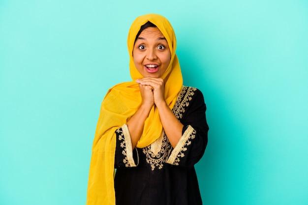 Jonge moslimvrouw op blauw bidden voor geluk, verbaasd en mond openen op zoek naar voren.