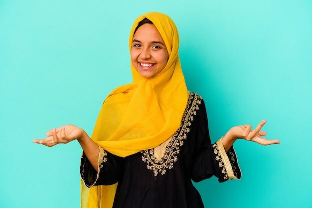 Jonge moslimvrouw op blauw met een welkome uitdrukking.