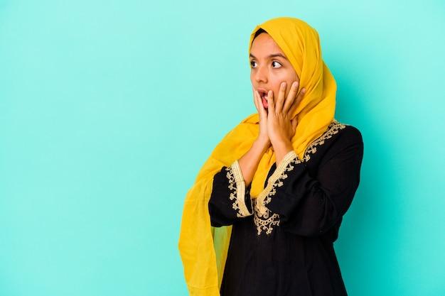 Jonge moslimvrouw op blauw schreeuwt luid, houdt ogen open en handen gespannen.
