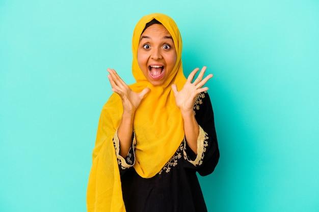 Jonge moslimvrouw op blauw viert een overwinning of succes, hij is verrast en geschokt.
