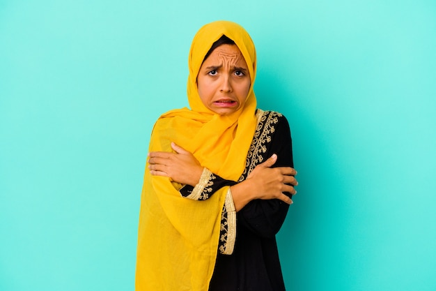 Jonge moslimvrouw op blauw wordt koud als gevolg van een lage temperatuur of een ziekte.