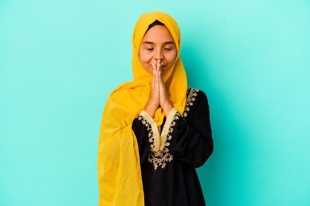 Jonge moslimvrouw op blauwe hand in hand bid dichtbij mond, voelt zich zelfverzekerd.