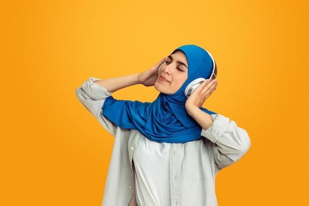 Jonge moslimvrouw op gele achtergrond Gratis Foto