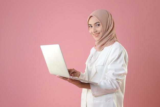 Jonge moslimvrouw werkt online op een laptop