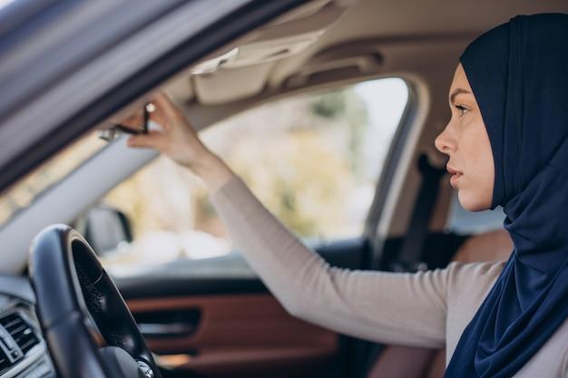 Jonge moslimvrouw zit in haar auto en kijkt in de spiegel