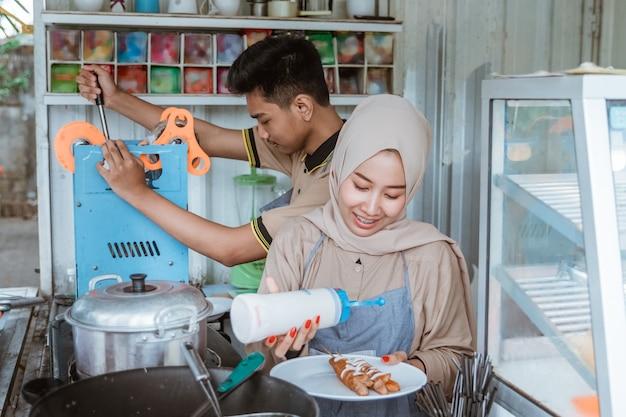Jonge moslimvrouwen en -vrouwen die een gerecht bereiden dat door de klant is besteld