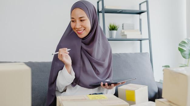 Jonge moslimzakenvrouw controleert productaankooporder op voorraad en bewaart op tabletcomputerwerk op kantoor aan huis.