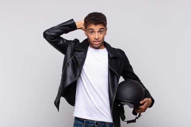 Jonge motorrijder die zich gestrest, bezorgd, angstig of bang voelt, met de handen op het hoofd, in paniek raakt bij vergissing
