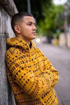 Jonge multi-etnische aziatische man in de straten buiten