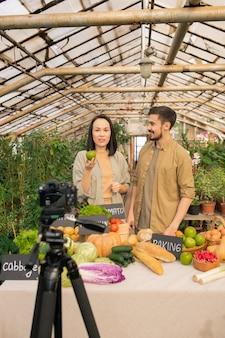 Jonge multi-etnische bloggers staan aan de balie vol met eten en leren producten voor de camera te kiezen