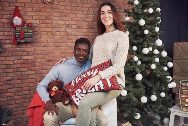 Jonge multi-etnische kerstmis die van de paarvergadering huis koesteren. nieuwjaar. feestelijke sfeer van een man en een vrouw