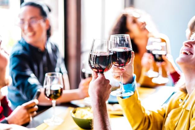 Jonge multi-etnische mensen die rode wijn drinken en roosteren tijdens het lunchfeest