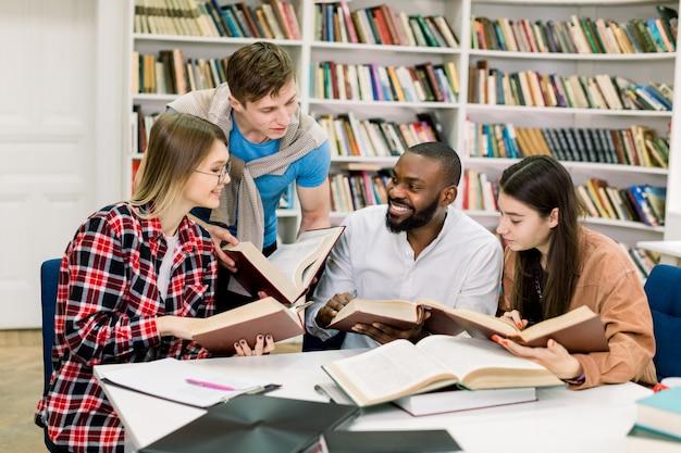 Jonge multi-etnische vrienden, twee vrouwen en twee mannen, praten met elkaar en glimlachen terwijl het lezen van boeken aan tafel in de moderne bibliotheek op de campus