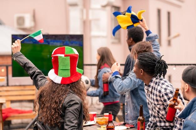 Jonge multiculturele groep fans kijken naar uitzending van sportwedstrijd op terras in stedelijke omgeving