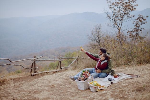 Jonge multiculturele paar verliefd zittend op deken op picknick en genieten van champagne. herfst tijd.