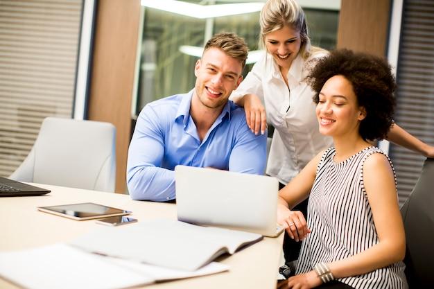 Jonge multiraciale mensen die op het kantoor werken