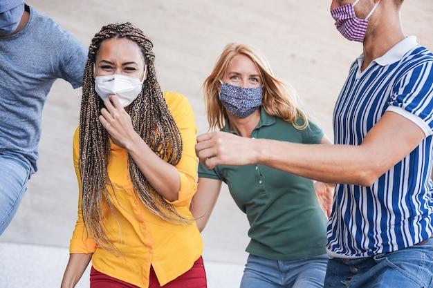 Jonge multiraciale mensen die plezier hebben met het dragen van een veiligheidsmasker buiten in de stad - focus op het gezicht van een afrikaans meisje