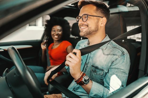 Jonge multiraciale paar zitten in een auto en veiligheidsgordels vastmaken.