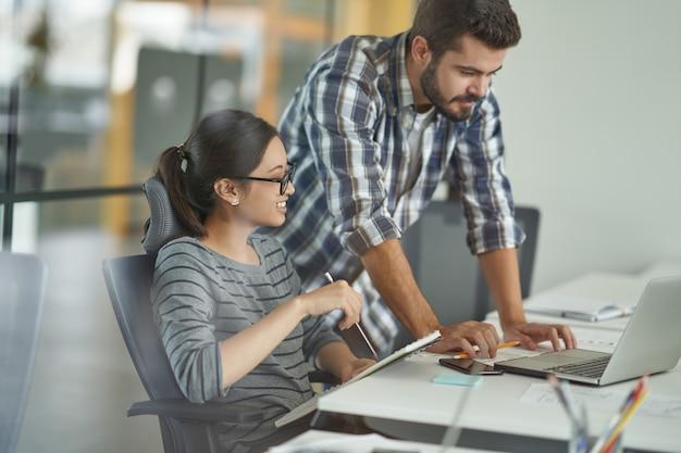Jonge multiraciale vrouwelijke en mannelijke collega's die naar het scherm van de laptop kijken en het project bespreken