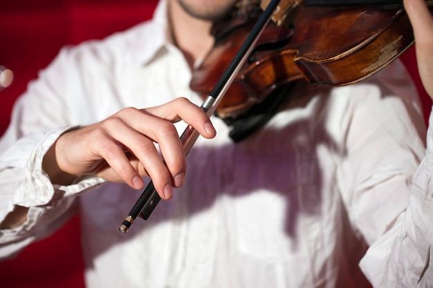 Jonge musicus die de viool in een restaurant op een rode muur speelt.