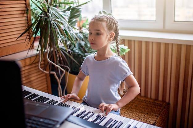 Jonge musicus die klassieke digitale piano thuis speelt tijdens online klasse thuis, zelfisolatie