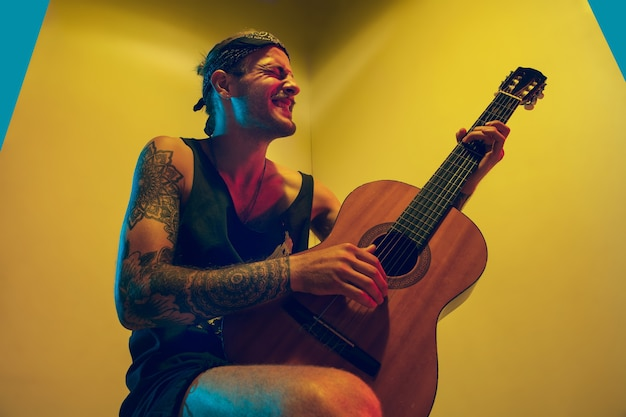 Jonge musicus die op kleurrijke muur in neonlicht presteert