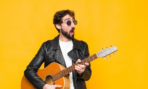 Jonge musicusmens die, gelukkige gedachten en ideeën, dagdromen, die aan kant met een gitaar kijken benieuwd zijn