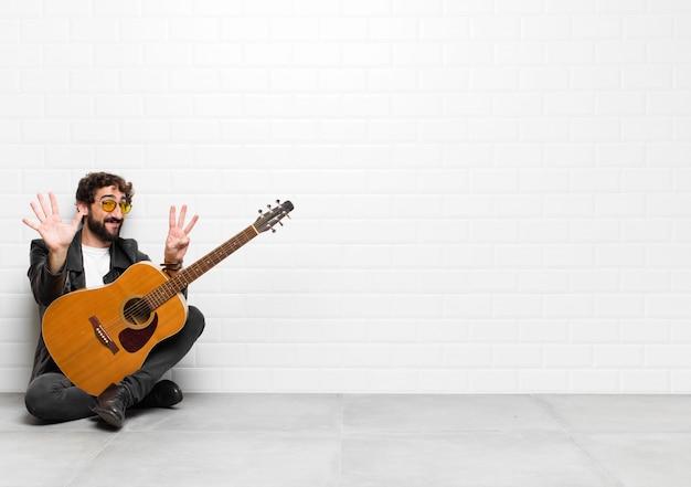 Jonge musicusmens die vriendelijk glimlacht en kijkt, nummer acht of achtste met vooruit hand toont, aftellend met een gitaar, rock and roll-concept