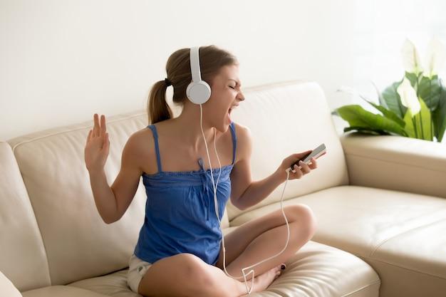 Jonge muziekventilator die hoofdtelefoons het zingen draagt