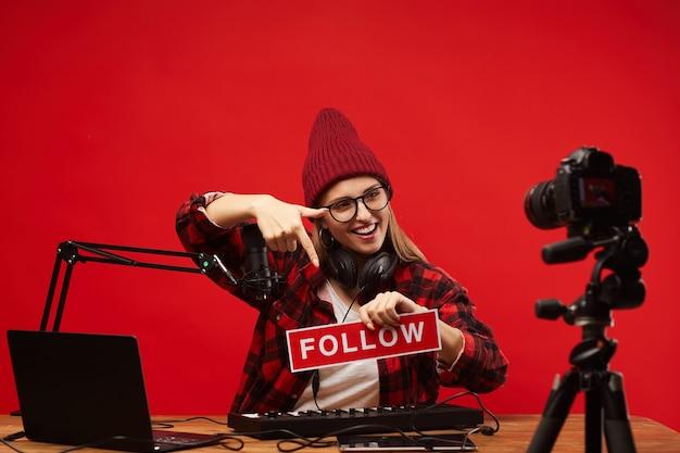 Jonge muzikale blogger wijzend op plakkaat in haar handen en online communiceren met haar volgelingen
