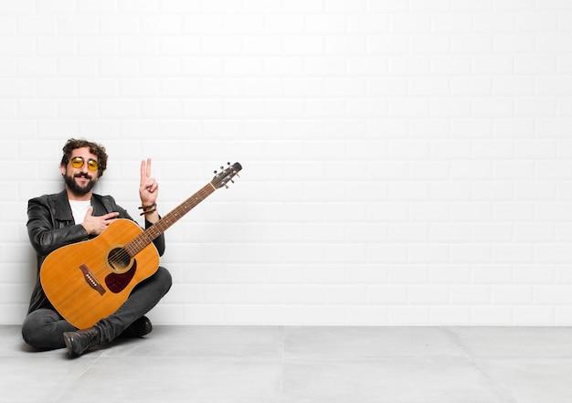 Jonge muzikant die er gelukkig, zelfverzekerd en betrouwbaar uitziet, glimlachend en overwinningsteken toont, met een positieve houding met een gitaar-, rock-'n-roll-concept