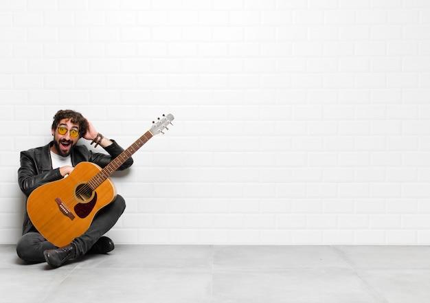 Jonge muzikant die er gelukkig, zorgeloos, vriendelijk en ontspannen uitziet en geniet van het leven en succes, met een positieve instelling met een gitaar-, rock-'n-roll-concept
