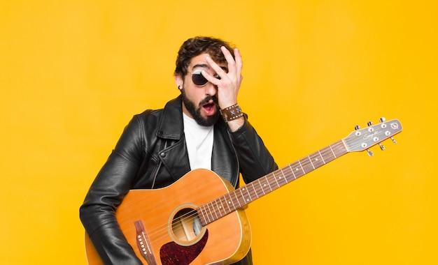 Jonge muzikant die geschokt, bang of doodsbang kijkt, gezicht bedekt met hand en tussen vingers gluurt met een gitaar, rock-'n-roll-concept
