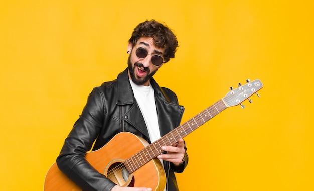Jonge muzikant die zich verbaasd en verward voelt, met een domme, verbijsterde uitdrukking kijkt naar iets onverwachts met een gitaar-, rock-'n-roll-concept