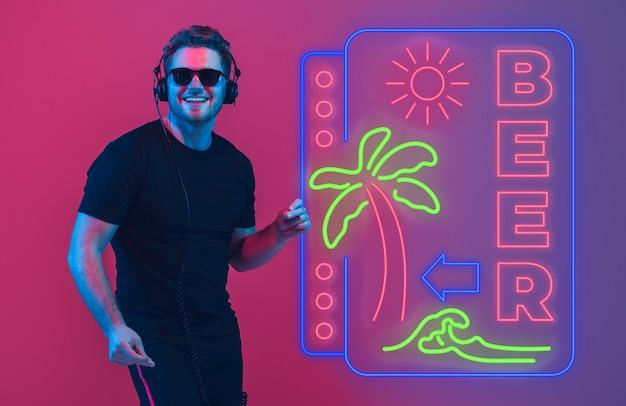 Jonge muzikant, feestgastheer die zingt op de achtergrond van de gradiëntstudio in neon met teken bier. concept van muziek, hobby, festival, zomer, vakantie, resort. boven staan. kleurrijk portret van kunstenaar.