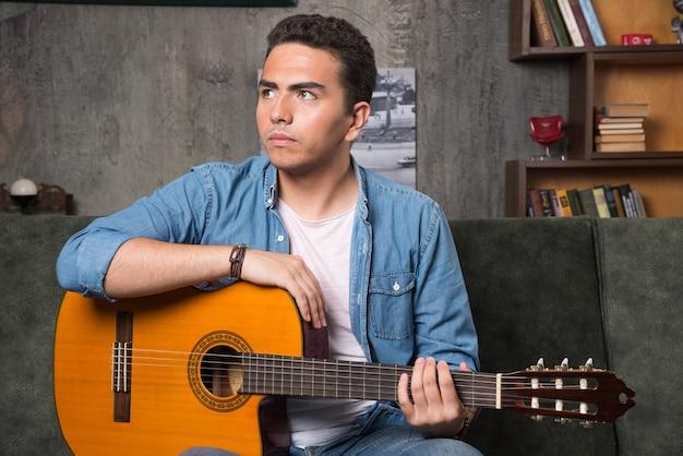 Jonge muzikant gitaar houden en zittend op de bank. hoge kwaliteit foto