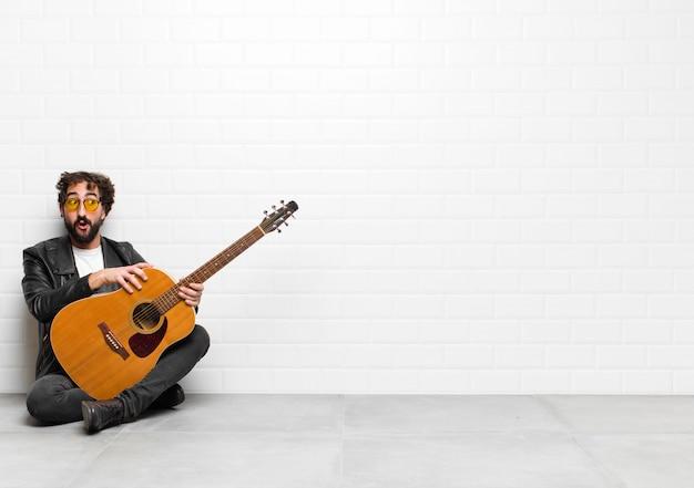 Jonge muzikant man geschokt, blij, verbaasd en verrast, op zoek naar de kant met open mond met een gitaar, rock and roll concept
