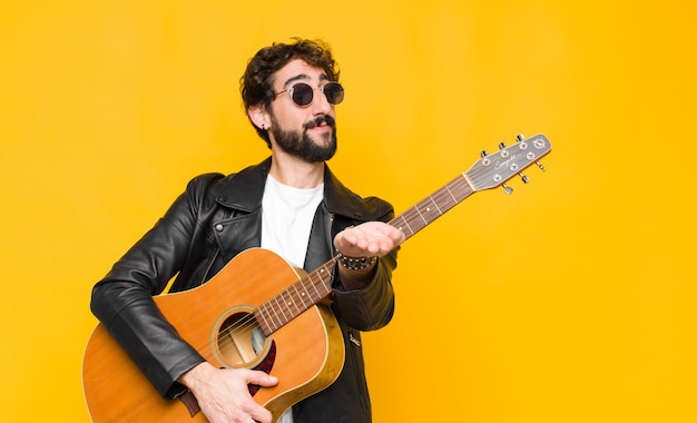 Jonge muzikant man glimlachend gelukkig met vriendelijke, zelfverzekerde, positieve blik, aanbieden en tonen van een object of concept met een gitaar, rock and roll concept