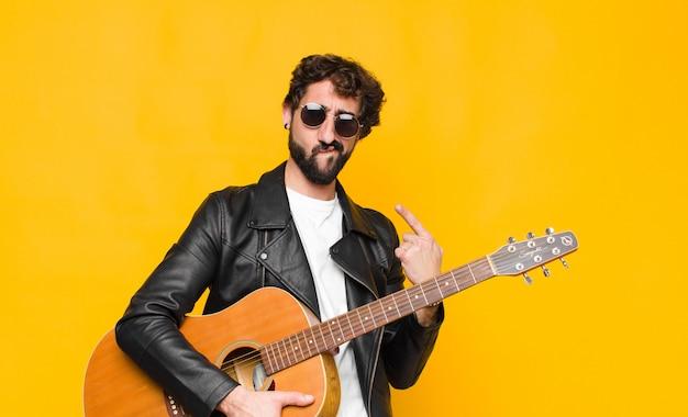 Jonge muzikant-man met een slechte houding die trots en agressief kijkt, naar boven wijst of een leuk teken maakt met handen met een gitaar-, rock-'n-roll-concept