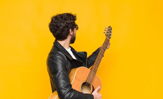 Jonge muzikant man permanent en wijst naar object op kopie ruimte, achteraanzicht met een gitaar, rock and roll concept